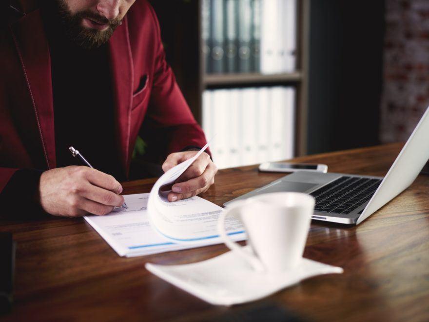 Unrecognizable businessman signing a document at office