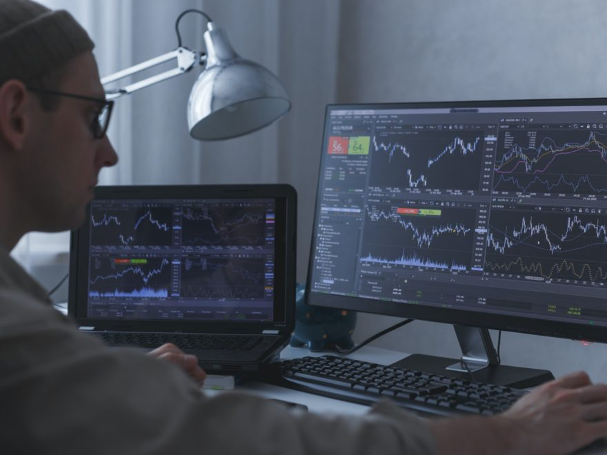 Thoughtful serious trader broker analyzing stock market graphs at pc and laptop